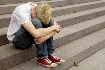 upset young blond man sitting on stairs laying his hand on his arm