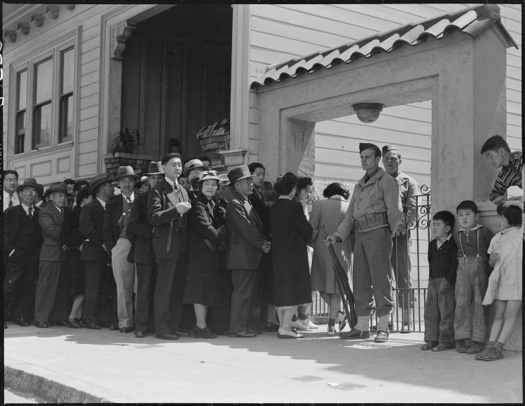 Japanese family heads and persons living alone, form a line outside Civil Control Station located in the Japanese American Citizens League Auditorium at 2031 Bush Street, to appear for