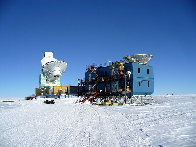 The Dark Sector Laboratory at Amundsen-Scott South Pole Station. At left is the South Pole Telescope. At right is the BICEP2 telescope. Photo by Amble, 2009. CC-BY-SA-3.0 via Wikimedia Commons.