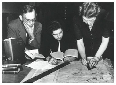 Bill Burke and Jane Mull, members of the Committee of the American Council of Learned Societies on the Protection of Cultural Treasures in War Areas, working with Gladys Hamlin, draftswoman, at the Frick Art Reference Library on a map of Paris. circa 1943-44. The Frick Collection/Frick Art Reference Library Photographs. [National Archives photograph]
