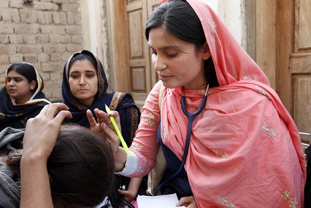 A female doctor with the International Medical Corps examines a woman patient at a mobile health clinic in Pakistan. Photo by DFID/Russell Watkins.; UK Department for International Development. CC BY 2.0 via DID Flickr
