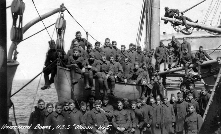 "Homeward bound troops pose on the ship's deck and in a lifeboat, 1919. The original image was printed on postal card (""AZO"") stock. Public Domain"