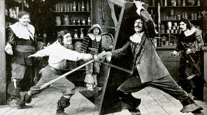Still from the American film The Three Musketeers (1921) with George Siegmann, Douglas Fairbanks, Eugene Pallette, Charles Belcher, and Léon Bary, on page 24 of Peter Milne, Motion Picture Directing; The Facts and Theories of the Newest Art (1922).