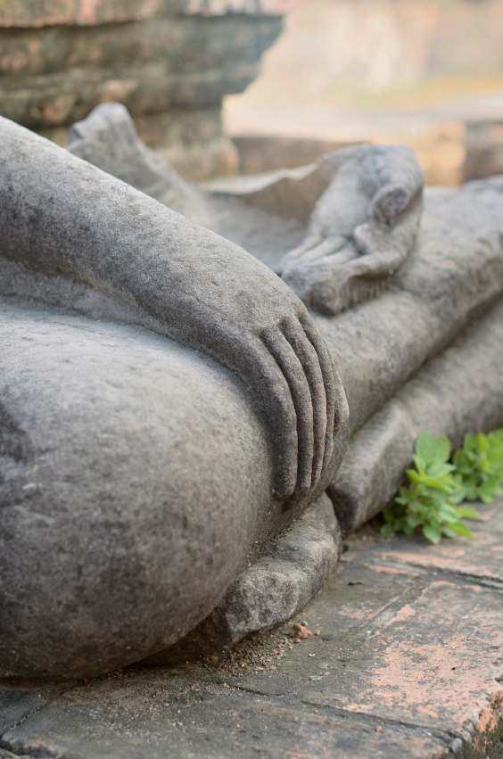 Detail of the hands of an ancient stone Buddha statue. © Natalia_Kalyatina via iStockphoto