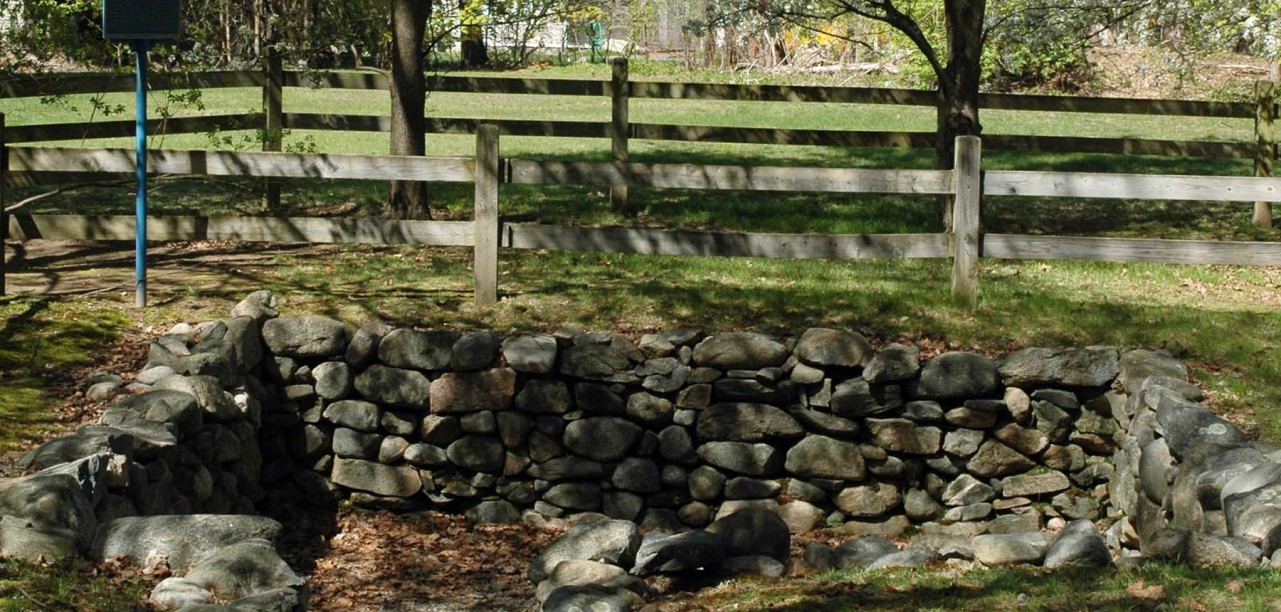 Cellar of the Salem Village Parsonage, in present-day Danvers, Massachusetts. The parsonage was built for George Burroughs in 1681. The new parsonage that replaced it in 1784 is in the background. Photo by Emerson W. Baker.