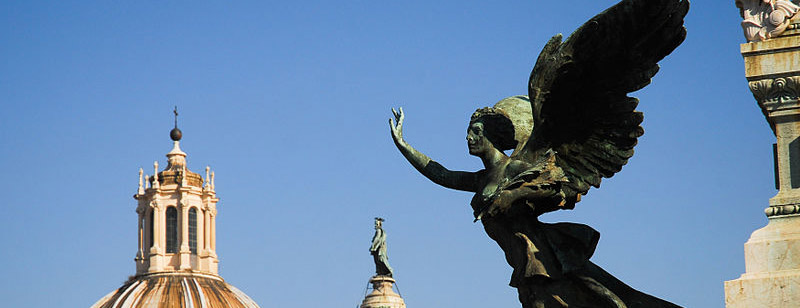 800px-Winged_Victory_(Nike)_bronze_statue_against_background_of_Trajan's_Column_and_dome_of_Santa_Maria_di_Loreto_church._Rome,_Italy