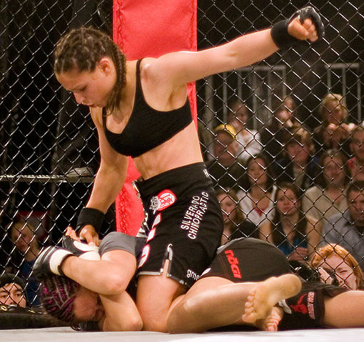 Gina Carano in full mount position performing ground and pound. Photo by Matthew Walsh. CC BY-SA 2.0 via Wikimedia Commons.